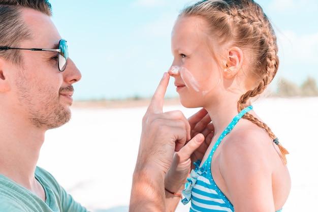 Отец, применяя солнцезащитный крем к носу дочери.