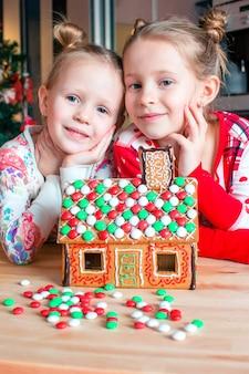 飾られたリビングルームの暖炉のそばでクリスマスのジンジャーブレッドの家を作る小さな女の子。