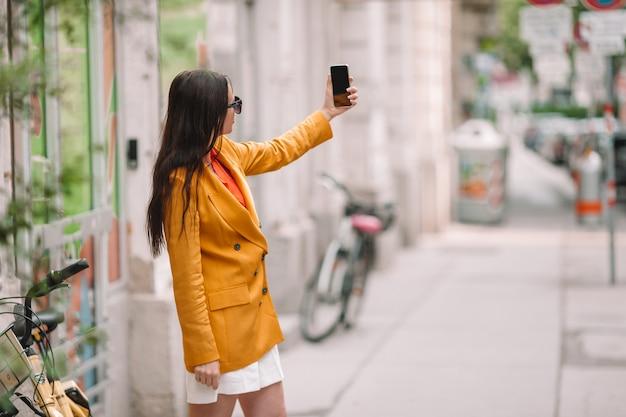 女性は都市で彼女のスマートフォンで話します。イタリアの都市で屋外の若い魅力的な観光客
