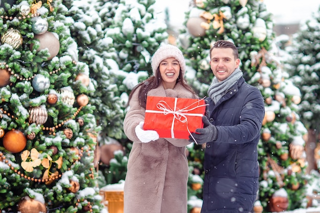 街でクリスマスを祝って、お互いに贈り物を与える若い美しい陽気なカップル。