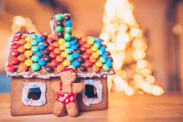 ジンジャーブレッドの妖精の家、花輪と明るいクリスマスツリーの