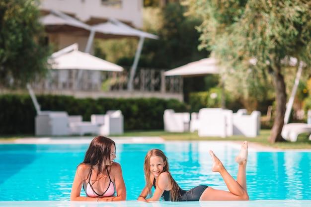 ママと小さな娘の家族が豪華なスイミングプールで夏休みを楽しんでいます