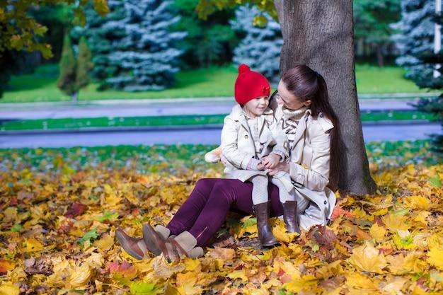 ファッションの若い母親と秋の公園で晴れた日を楽しんでいる彼女の愛らしい小さな娘