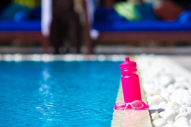 スイミングプールのそばのピンクのスポーティな水のボトル