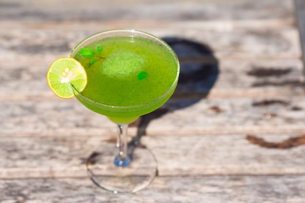 熱帯の白いビーチで緑のおいしいカクテル