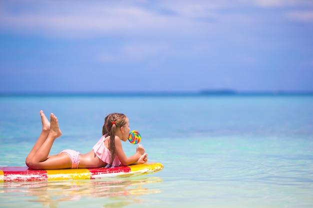 ロリポップを持つ少女は、海でサーフボードで楽しい時を過す