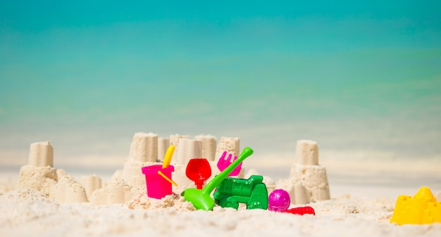 プラスチックの子供のおもちゃと白いビーチで砂の城