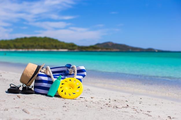 ビーチでのストライプバッグ、麦わら帽子、日焼け止め、タオル