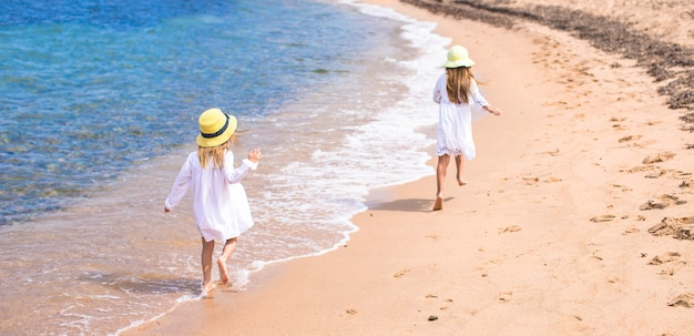 愛らしいかわいい女の子が休暇中に白いビーチで楽しい時を過す