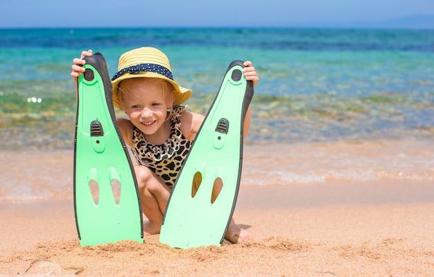 足ひれとビーチでシュノーケリングのゴーグルを持つ少女