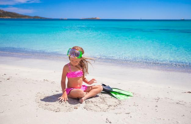 Маленькая девочка с ластами и очки для подводного плавания