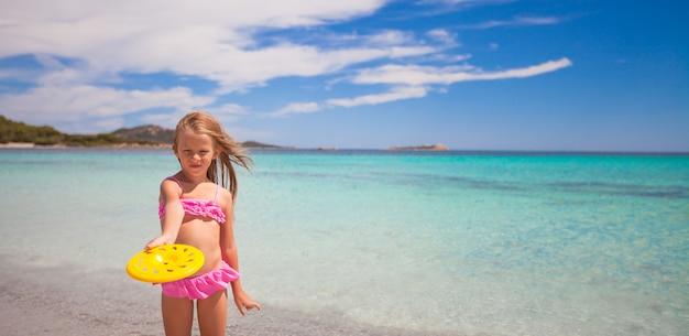 海で熱帯の休暇中にフリスビーを遊ぶ少女