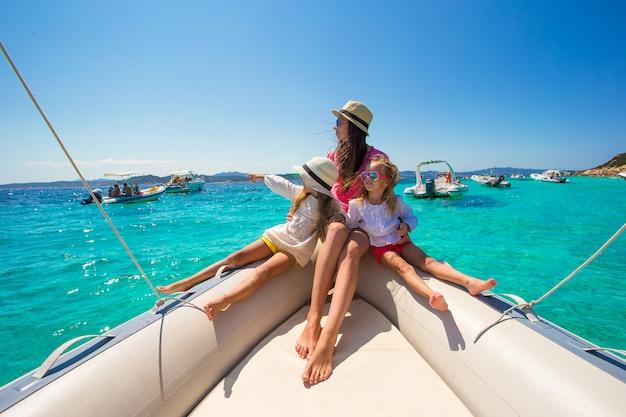 Молодая мать с ее очаровательными девочками отдыхает на большой лодке