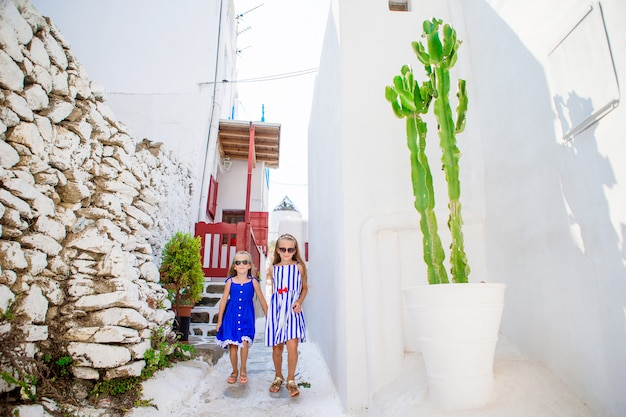 Две девушки в голубых платьях веселятся на свежем воздухе. дети на улице типичной греческой традиционной деревни с белыми стенами и красочными дверями на острове миконос, в греции