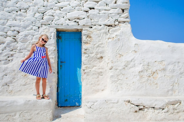 Милая девушка в голубом платье, развлечения на открытом воздухе возле церкви парапортиани. ребенок на улице типичной греческой традиционной деревни с белыми стенами и красочными дверями на острове миконос, в греции