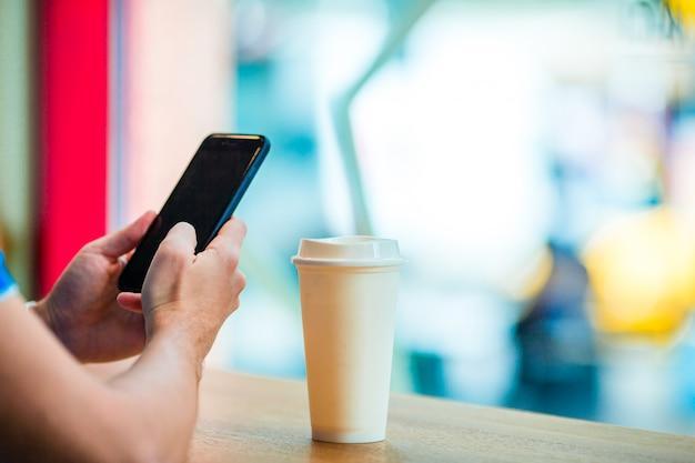カフェで携帯電話とコーヒーのガラスを保持している男性の手のクローズアップ。