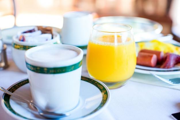 Здоровый завтрак со свежим соком и сладким круассаном в ресторане курорта под открытым небом