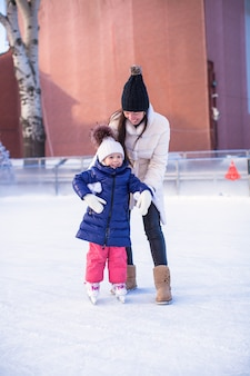 Маленькая прелестная девушка с мамой учится кататься на коньках
