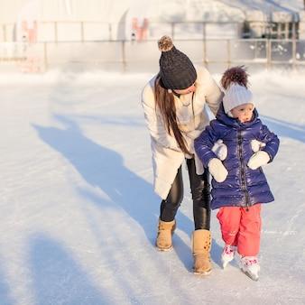 Счастливая взволнованная маленькая девочка и ее молодая мать учатся кататься на коньках
