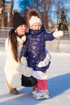 Молодая мать и ее милая маленькая дочь на катке
