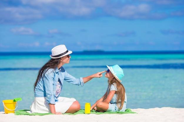 熱帯のビーチで彼女の娘に日焼け止めクリームを適用する母