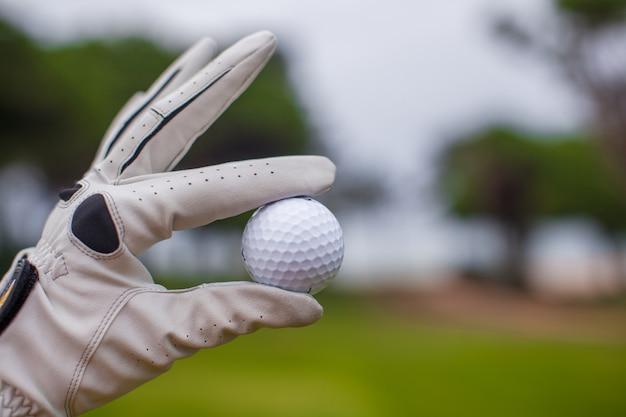 彼の手でゴルフボールを保持しているゴルフプレーヤー男
