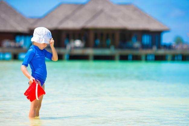 熱帯の休暇中にビーチおもちゃで遊ぶ愛らしい少女