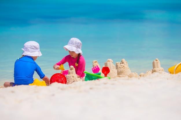 Маленькие девочки играют с пляжными игрушками во время тропического отпуска