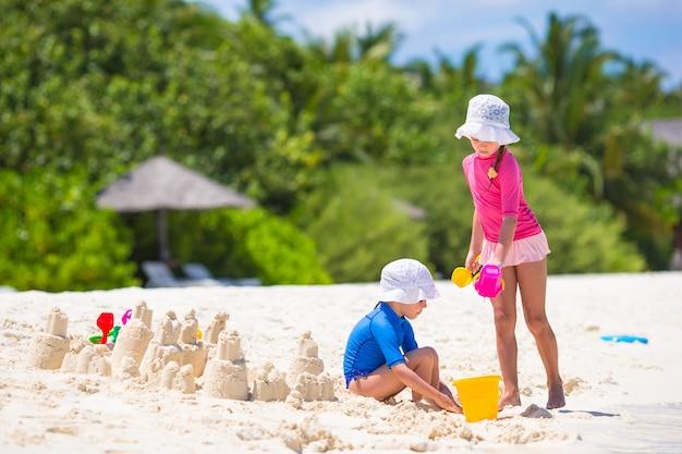 熱帯の休暇中にビーチおもちゃで遊ぶ女の子