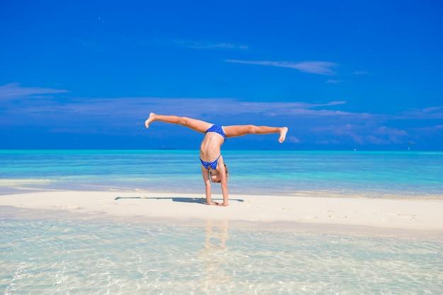 熱帯の白い砂浜で腕立て側転を楽しんで愛らしい少女