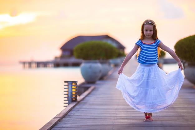 夕暮れ時の木製の桟橋に愛らしい少女のシルエット