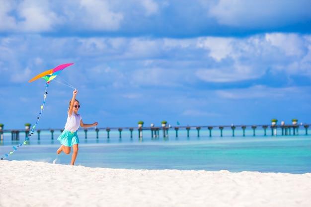 熱帯のビーチでカイトを飛行と遊んで幸せな少女