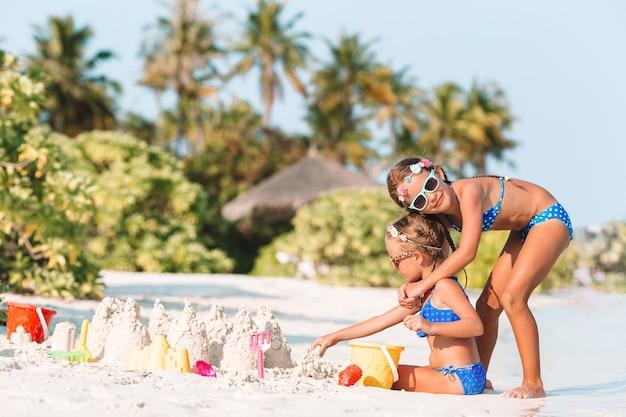 Счастливые маленькие девочки играют с пляжными игрушками во время тропического отпуска