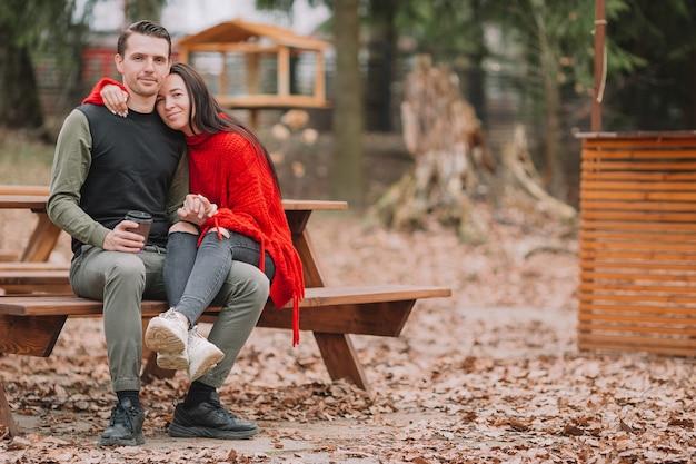 カフェの本格的なテーブルで屋外の公園で若いカップル