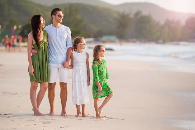 子供と幸せな家庭がビーチの上を歩く