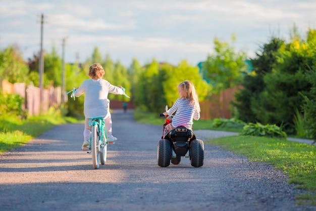 Счастливые маленькие девочки на велосипедах на открытом воздухе в парке