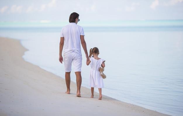 お父さんと夏休みの間にぬいぐるみを持つ少女