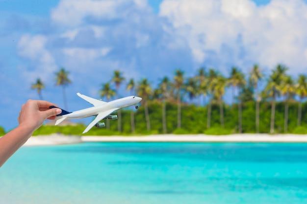 ターコイズブルーの海の背景に飛行機の小さな白いミニチュア