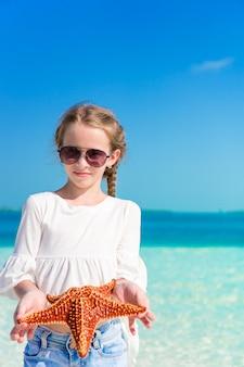 白い空のビーチのヒトデでのかわいい女の子