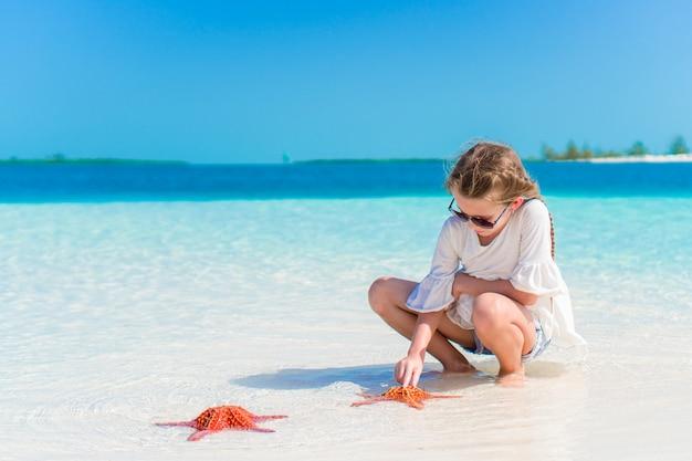 白いビーチのヒトデでのかわいい女の子