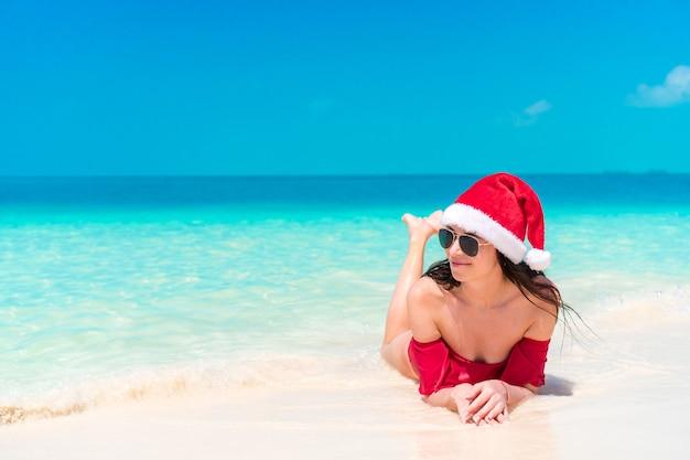 Молодая женщина, наслаждаясь солнцем, загорая на идеальный бирюзовый океан.