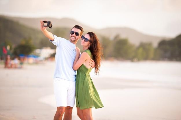 幸せなカップルの新婚旅行の休日に白いビーチで写真を撮る