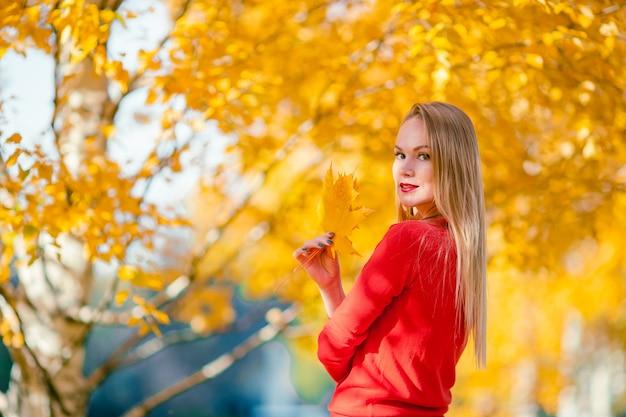 秋の公園で葉を持つ若い女