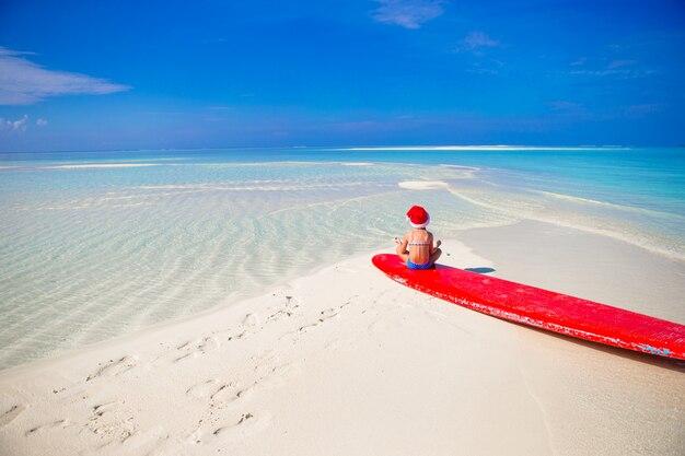 休暇中にビーチでサンタ帽子でのかわいい女の子