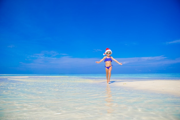 休暇中にビーチでサンタ帽子で幸せな少女