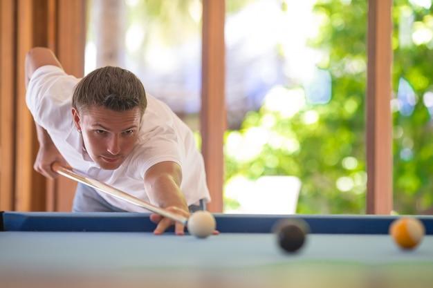 Молодой человек играет в бильярд на летних каникулах
