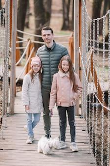 Отец и милые дочери с собакой на открытом воздухе
