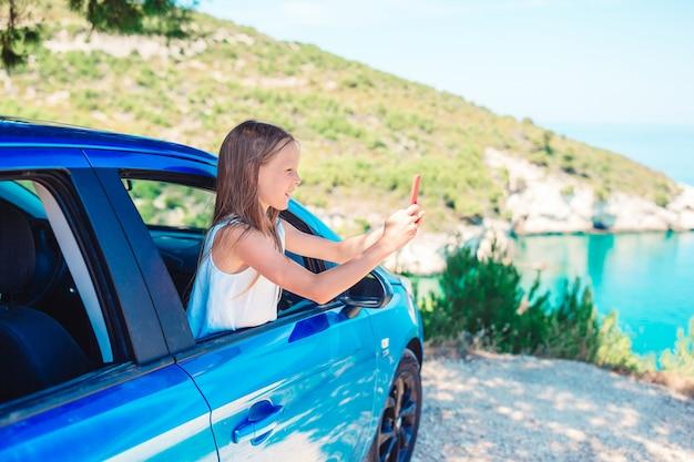 車での休暇旅行の少女