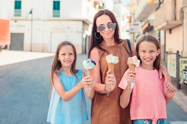 アイスクリームを食べる小さなかわいい娘を持つ母