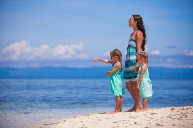 砂漠の島の熱帯の白いビーチで愛らしい小さな女の子や若い母親
